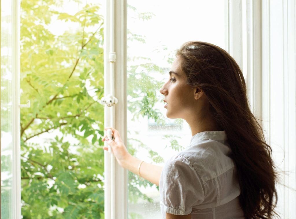 Junge Frau schaut aus einem geöffnetem Fenster.