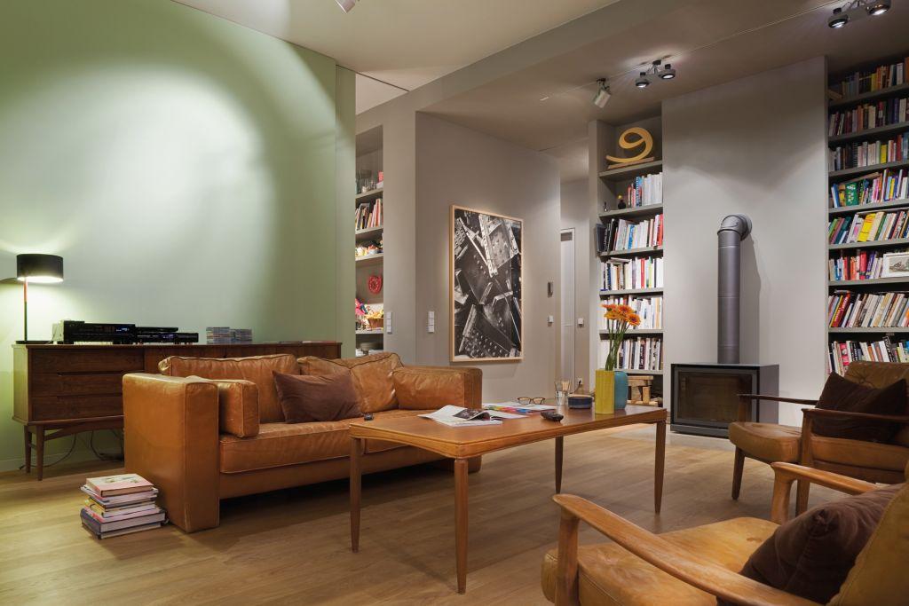 Wohnzimmer mit Couch und Bücherregal und Holztisch.