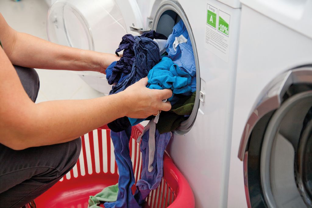 Hände nehmen Wäsche aus einer Waschmaschine
