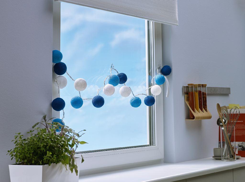 Lichterkette aus Garnkugeln hängen vor einem Fenster.