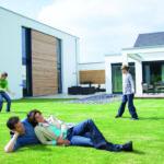 Ehepaar liegt vor dem Mehrgenerationenhaus auf dem Rasen, während die Kinder Fußball spielen.