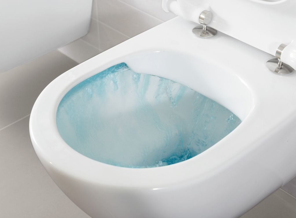 Eine Toilette ohne Spülrand, mit blau gefärbtem Spülwasser.
