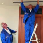 Zwei Facharbeiter installieren eine Klimaanlage, damit die Kunden ein angenehmes Wohnklima erhalten.