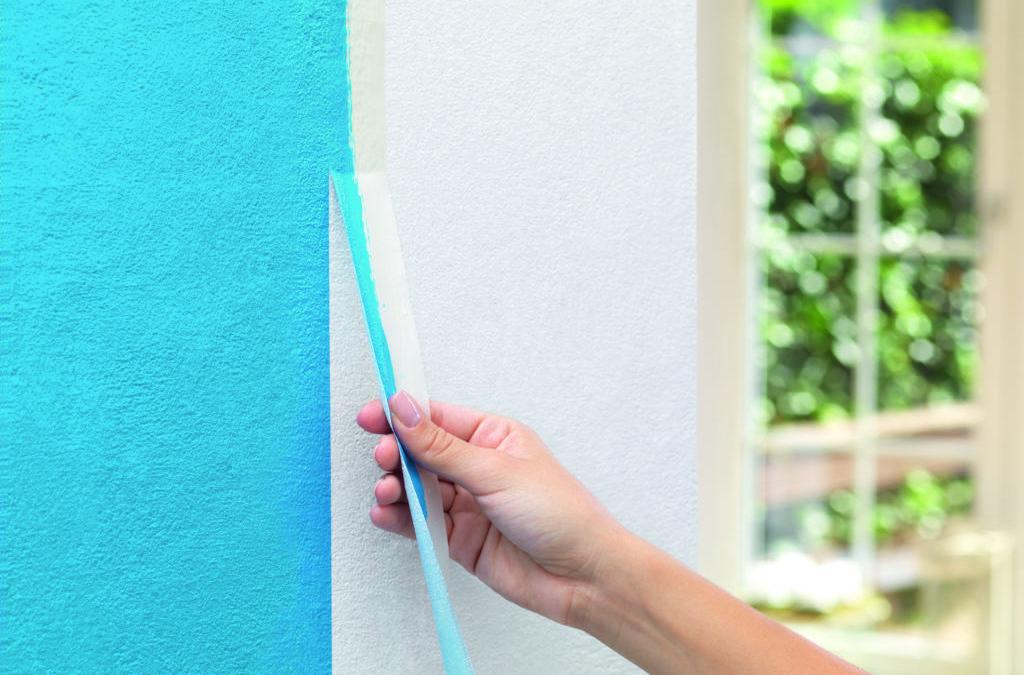 Malerband wird von der Wand abgezogen.