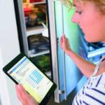 Strom sparen: Frau mit Tablet vor dem Kühlschrank