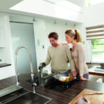 Paar kocht mit einer Kochfeldabsaugung in einer Wohnküche.