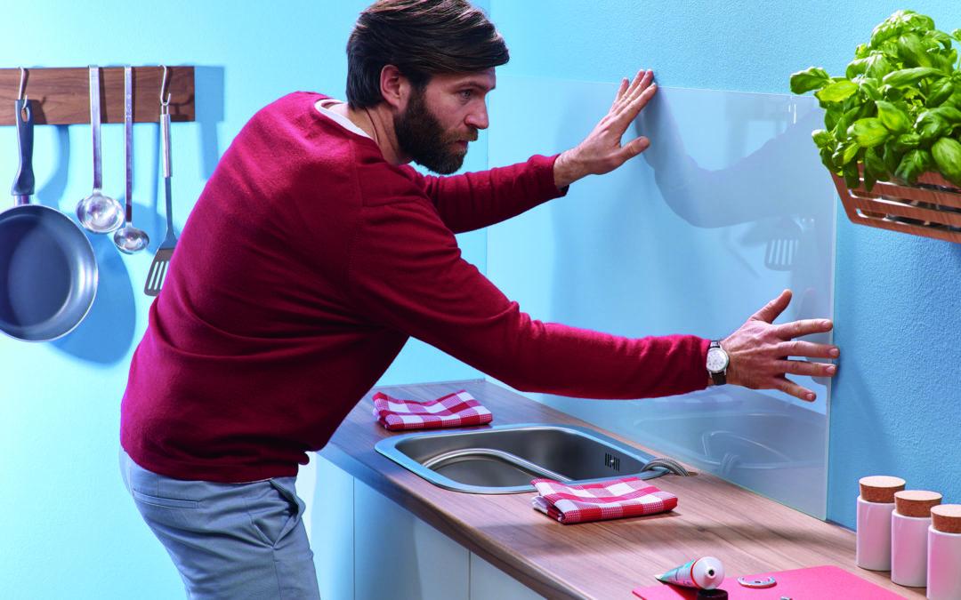 Mann befestigt eine Acrylplatte als Wandschutz.