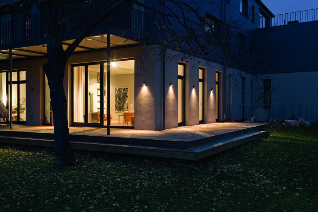 Durch die Hausautomation wirkt das Haus bewohnt, obwohl niemand Zuhause ist. (Haus mit beleuchteten Fenstern in der Nacht)