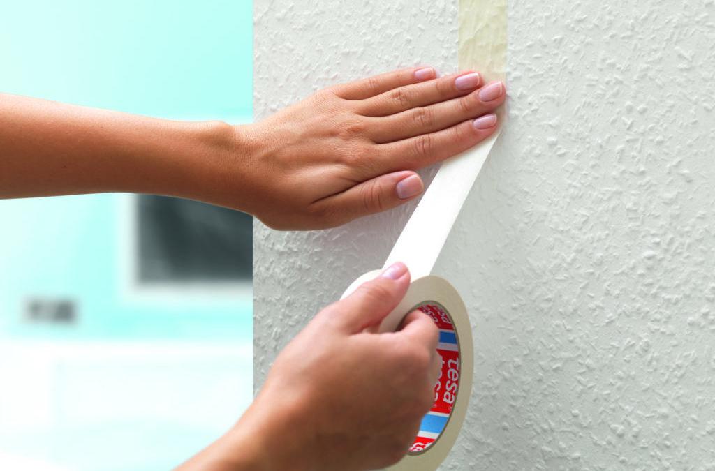 Ein Malerband wird an der Wohnwand befestigt, um später, nach dem Streichen, eine saubere Farbkante zu erhalten.
