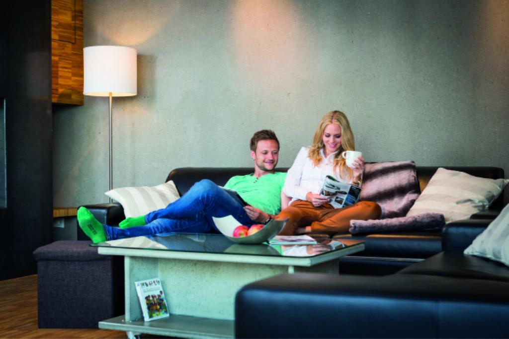 Ein Paar sitzt gemeinsam auf dem Sofa. Sie genießen das angenehme Raumklima in ihrer Wohnung.