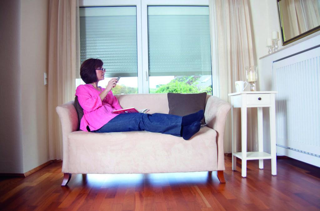 Eine Frau genießt die Barrierefreiheit in ihrem Eigenheim und bedient die Rollläden per Knopfdruck. Smart Home ermöglicht ihr dies.