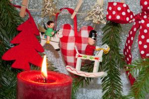 Hölzerner Baumschmuck neben einer echten brennenden Kerze. Hier ist die Brandgefahr groß.