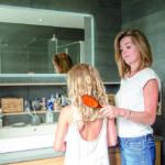 Eine Frau steht mit einem kleinen Mädchen vor dem Badezimmerspiegel und bürstet ihr die Haare. (Kleines Bad)
