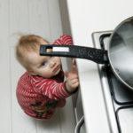 Kindersichere Küche: Ein Kleinkind versucht, an eine Bratpfanne heranzukommen, die auf dem Herd steht