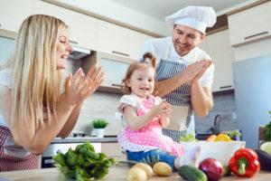 Eltern kochen gemeinsam mit einem Kleinein Kind (Kindersicheres Wohnen)