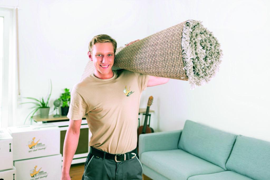 Ein Facharbeiter trägt einen zusammengerollten Teppich (Wohnungswechsel).