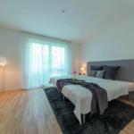 Ein modern eingerichtetes Schlafzimmer mit großem Bett. (Home Staging)