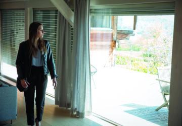 Eine Frau steht vor einem großen Fenster mit Rollladensteuerung.