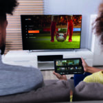 Ein Paar sitzt gemeinsam auf dem Sofa und schaut TV. Die Frau hält dabei ein Tablet in den Händen. (Streamingdienste)