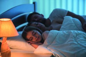 Eine Familie schläft ruhig in einem Bett (Hausstaubmilben).