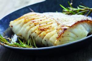 Gebratener Fisch auf einem Teller angerichtet (offene Wohnküche)