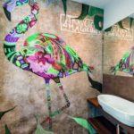 Auffällige Wandgestaltung im Badezimmer, in Form eines bunten Tieres.