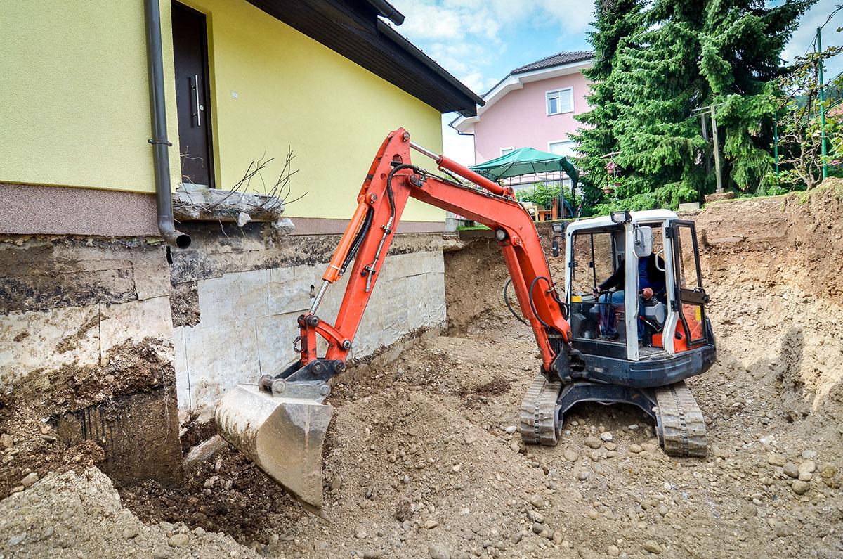 Dank eines Baggers wird eine Kellerwand von Erde befreit (Keller als Wohnraum).