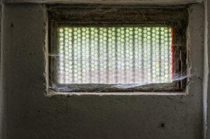 Ein altes Kellerfenster mit Spinnenweben (Keller als Wohnraum).