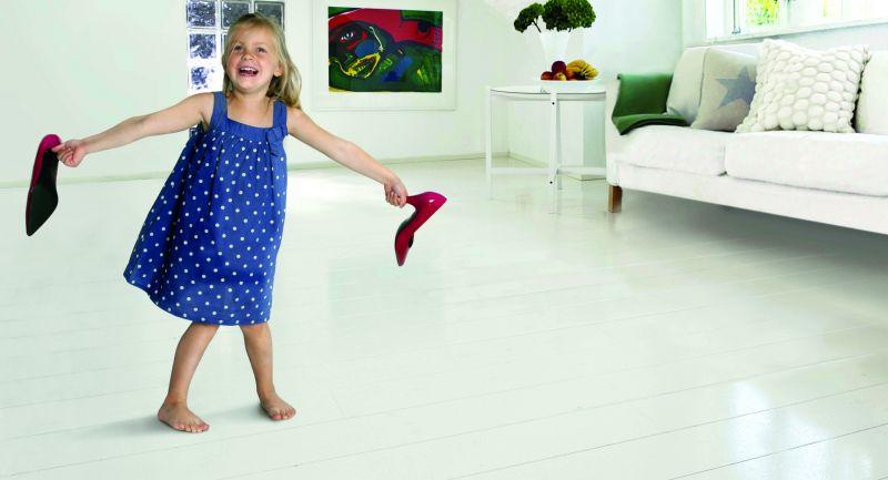 Ein kleines Mädchen läuft auf einem glänzenden Holzfußboden (Holzfußböden)