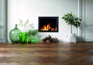 Kamin mit Feuer in einem Raum mit dunklem Parkett (Holzfußböden).