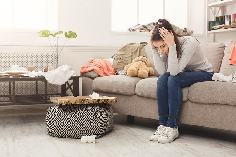 Eine Frau sitzt in einem unordentlichen Raum auf einem Sofa, hält sich die Hände an den Kopf und schaut unglücklich auf den Boden (Aufräumtipps).