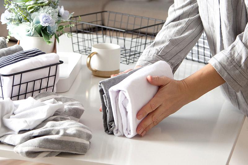 Eine Frau legt Textilien klein zusammen (Aufräumtipps)