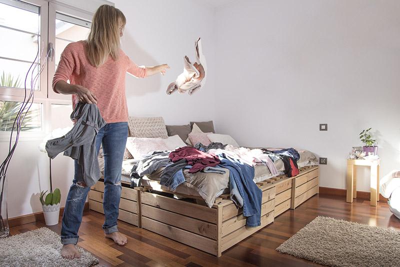 Eine blonde Frau wirft Kleidungsstücke auf das Bett (Aufräumtipps)