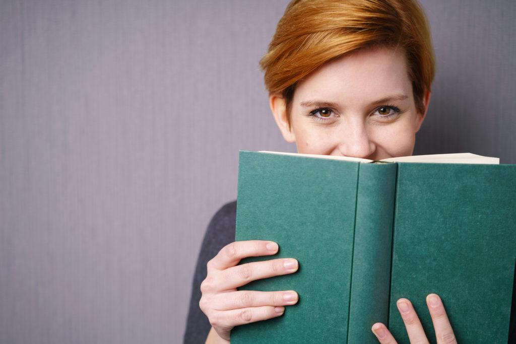 Eine Frau hält ein Buch vor ihr Gesicht und lächelt. (freiwillige Quarantäne)