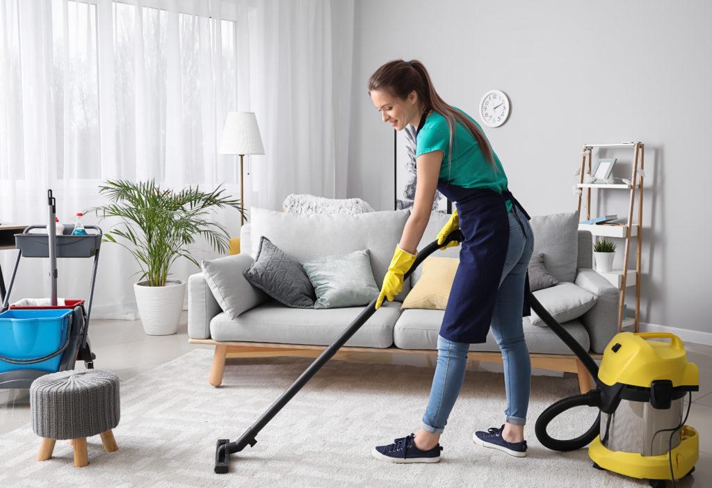 Eine Frau saugt in einem Wohnzimmer Staub und lächelt dabei. (freiwillige Quarantäne)