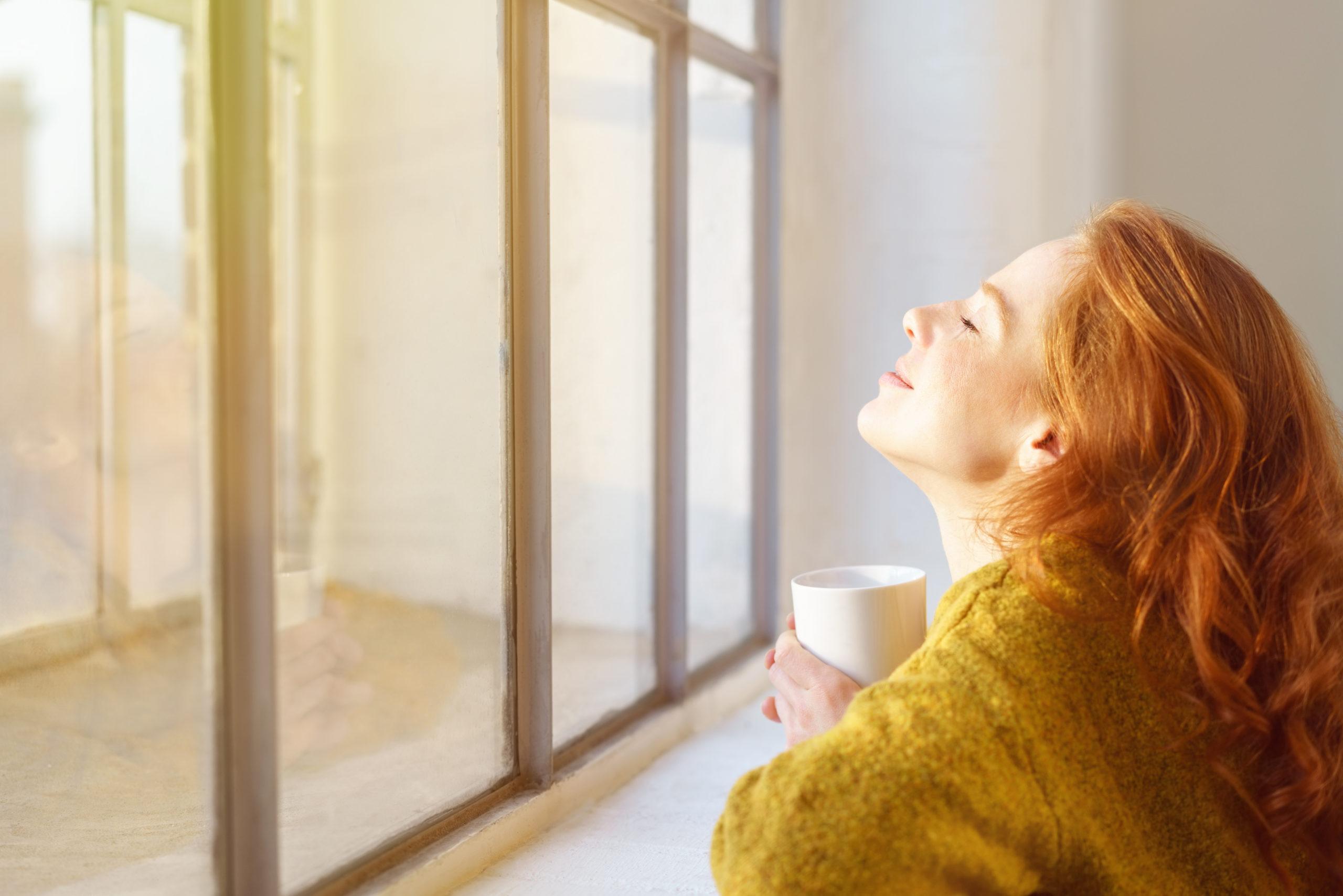 Eine Frau steht mit geschlossenen Augen vor einem Fenster, hat den Kopf in den Nacken gelegt und lächelt zufrieden. (freiwillige Quarantäne)