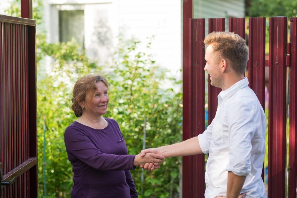 Nachbarschaftsstreit: eine Frau und ein Mann stehen sich gegenüber und reichen sich die Hände.