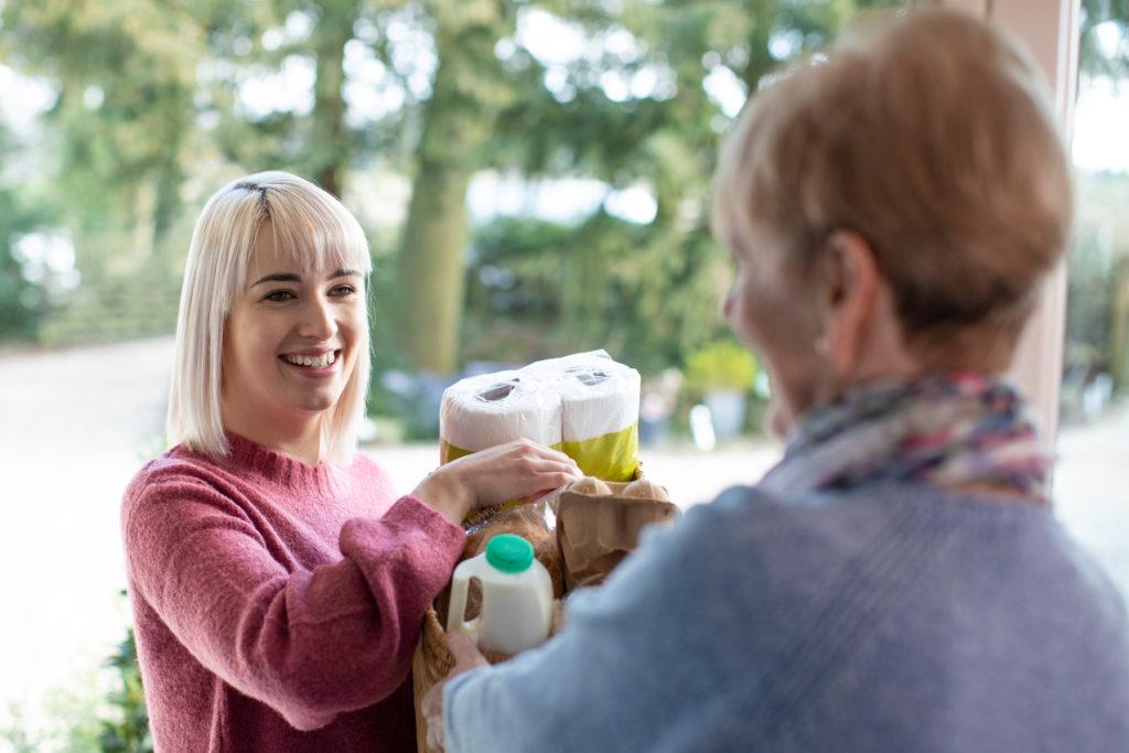 Nachbarschaftsstreit verhindern: eine junge Frau überreicht einer älteren Frau Einkäufe und lächelt dabei.
