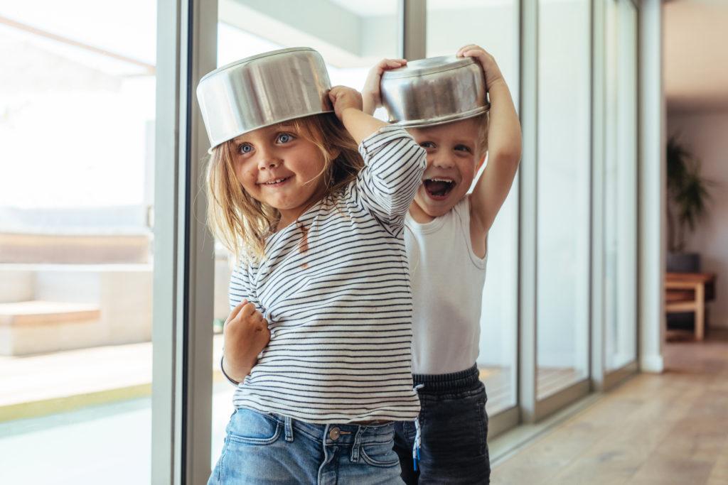 Zwei kleine Kinder haben einen Topf auf dem Kopf und lachen (laute Nachbarn).