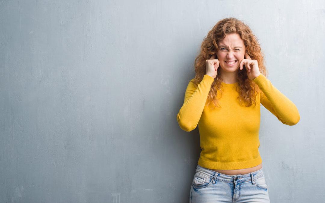 Laute Nachbarn: eine Frau steht an einer Wand angelehnt und hält sich dich Ohren zu.